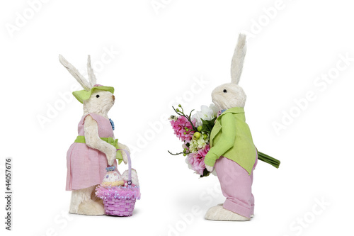 Side view of male Bunny with flower bouquet and female Rabbit over white background