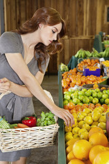 Beautiful young woman selecting fruit in market
