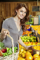 Portrait of a happy young woman shopping in market for fruits