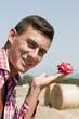 ritratto di ragazzo con rosa in mano tra il pagliaio