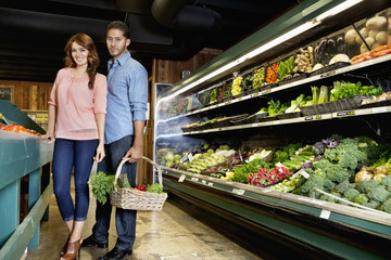 Portrait of young couple standing with vegetable basket in supermarket