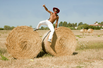 boy cowboy jumps on his bare chest by haystack