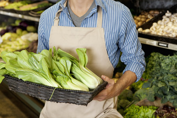 Midsection of man holding basket of bok choy in supermarket
