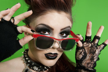 Portrait of young punk woman wearing sunglasses over green background