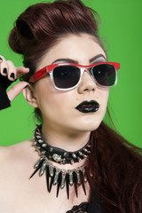Close-up of young punk woman wearing sunglasses over green background
