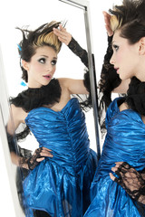 Beautiful young woman looking at herself in mirror