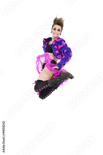 Happy young punk woman jumping over white background