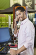 Portrait of a happy salesperson listening to telephone receiver in store