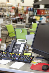 Computer with landline phone in store counter