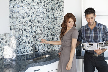 Young couple looking at color samples together in contemporary kitchen