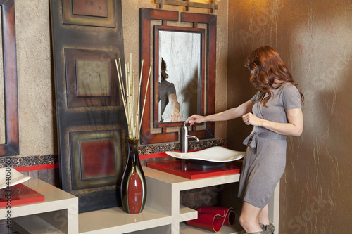 Young woman looking at modern faucet in model home