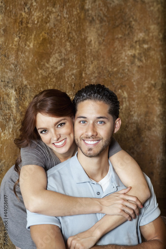 Portrait of happy young woman hugging man from behind