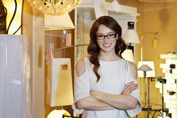 Happy young woman wearing glasses standing with arms crossed in store