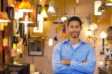 Portrait of a happy young man with arms crossed in lights store