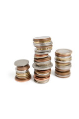 Close-up of stack of coins balancing over white background