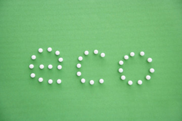 Close-up of push pins spelling eco over green background