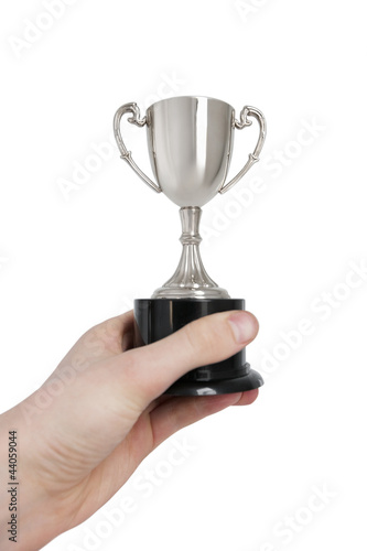 Cropped image of man's hand holding winning trophy over white background