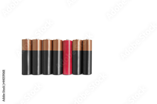 Red amid black batteries over white background