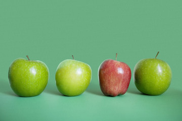 Row of red and green apples over colored background