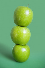 Stack of green apples over colored background