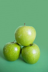 Close-up of green apples in pyramid stack over colored background