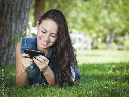 Mixed Race Young Female Texting on Cell Phone Outside