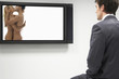 Businessman watching erotic naked couple on flat screen