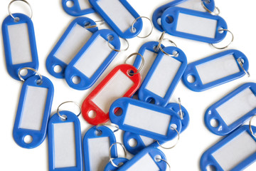Red tag ring with blue key rings over colored background