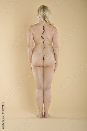 Rear view of a nude woman with a crack on spine standing over colored background