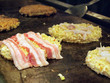 Cooking okonomi-yaki Japanese food with bacon and cuttlefish
