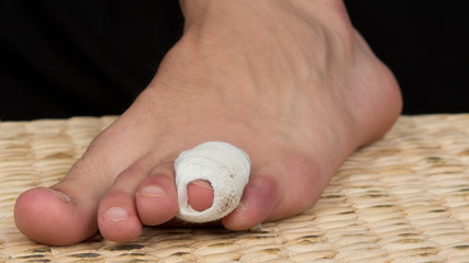 A bandage around a sore toe