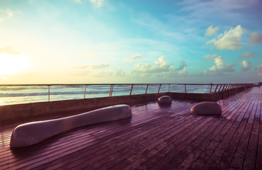 Stone benches and wooden deck besprinkled with sea water