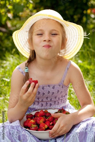 Little girl enjoys a ripe strawberry