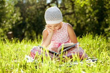 Charming girl in the hat reading a book