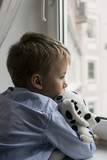 little boy with a toy near a window