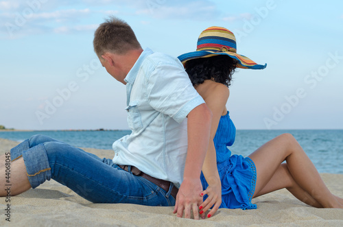 Couple sitting back to back on beach