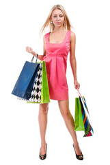 Young happy woman in pink dress with colorful shopping bags on a