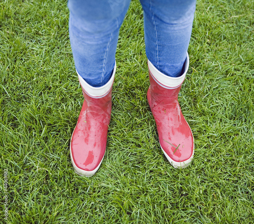 Teenage girl wearing red rubber boots