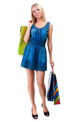 Young happy woman in blue dress with colorful shopping bags on a