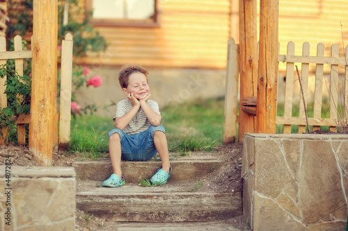 boy sits on a porch of the wooden house