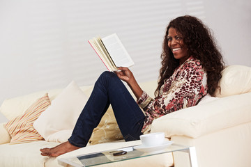 African lady reading a book on the sofa
