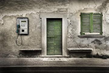 telefono pubblico contro casa abbandonata