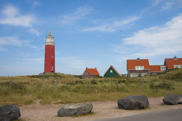 Red lighthouse, little houses and four stones on Texel island