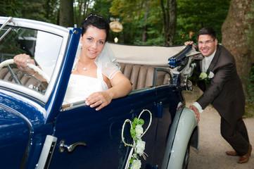 bräutigam schiebt das hochzeitsauto an