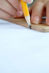 Women's hands are working with a pencil and ruler
