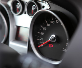 Car dashboard : An illuminated car dashboard in red and black