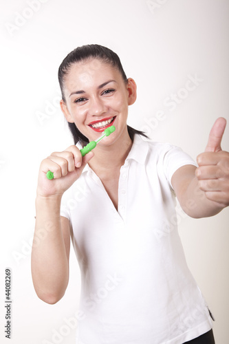 Young attractive girl cleaning her teeth and showing thumb up
