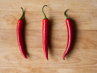 Three red chilli peppers on wood