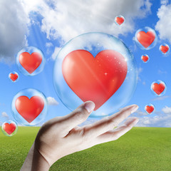 hand holds red heart in bubble