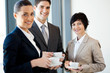 group of businesspeople having coffee during break in office